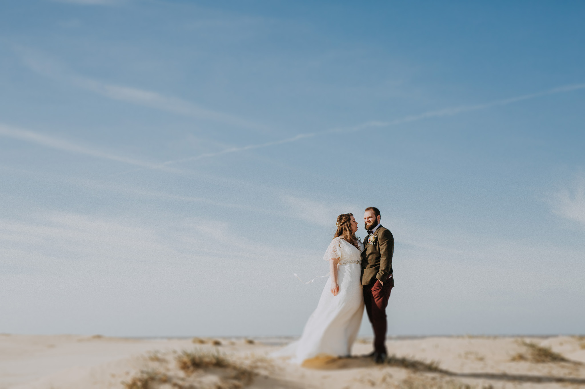 A bride and groom stand together on the sand at Wells next the sea