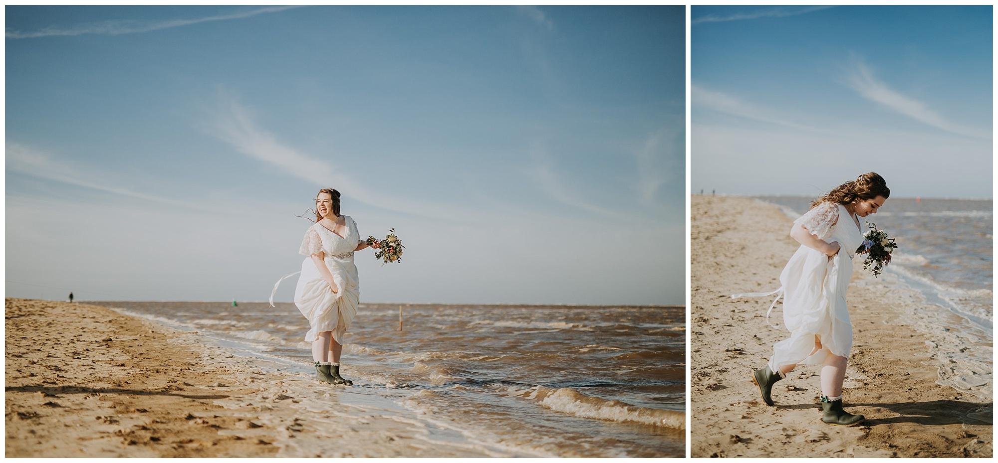 bride paddles in sea in wellies