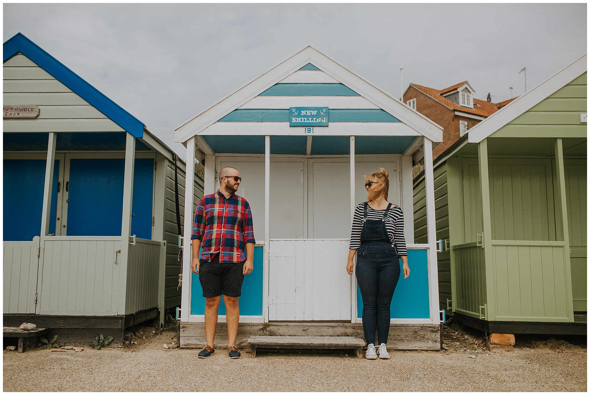 a couple laugh in front of southwold's beach huts