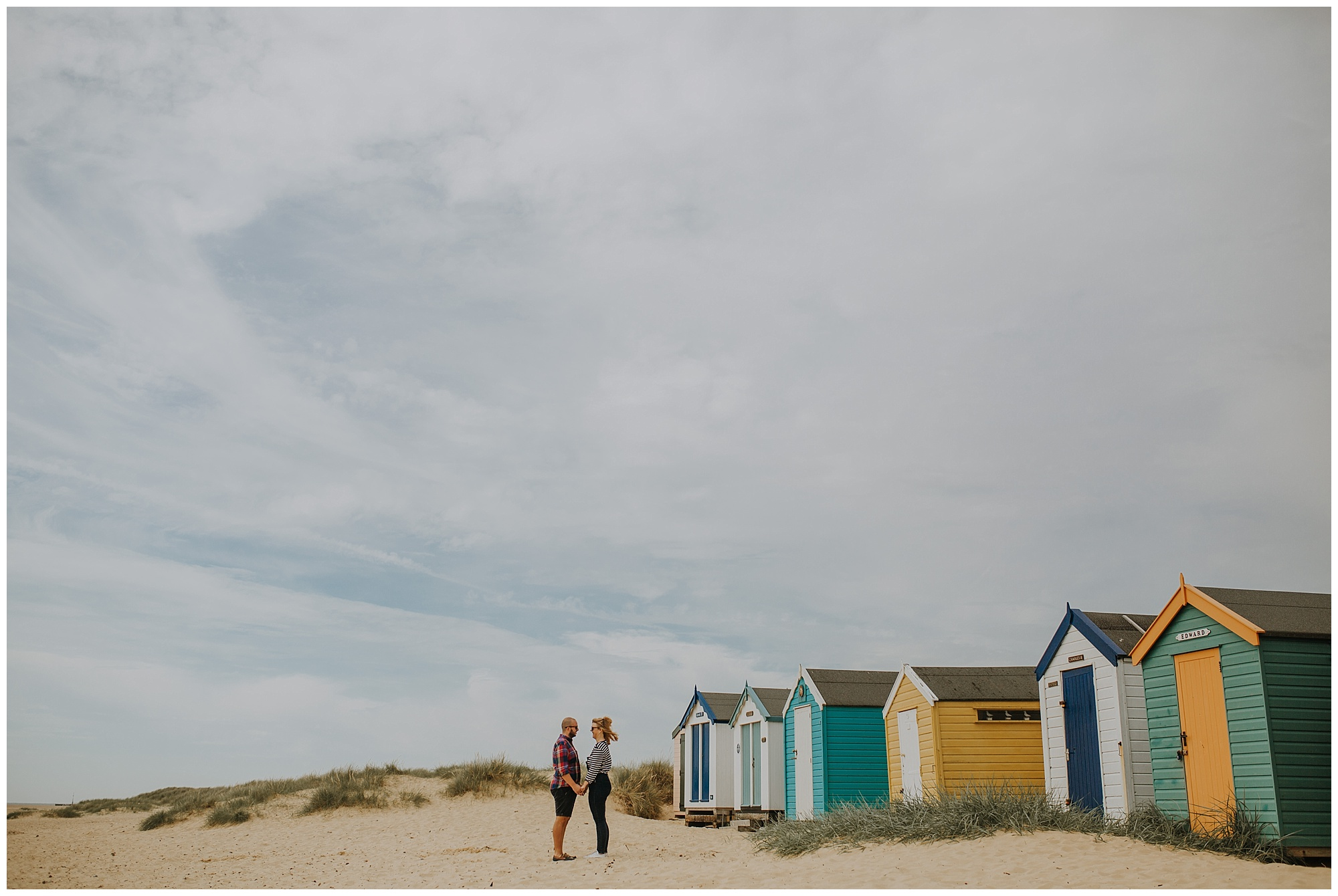 couple with beach huts