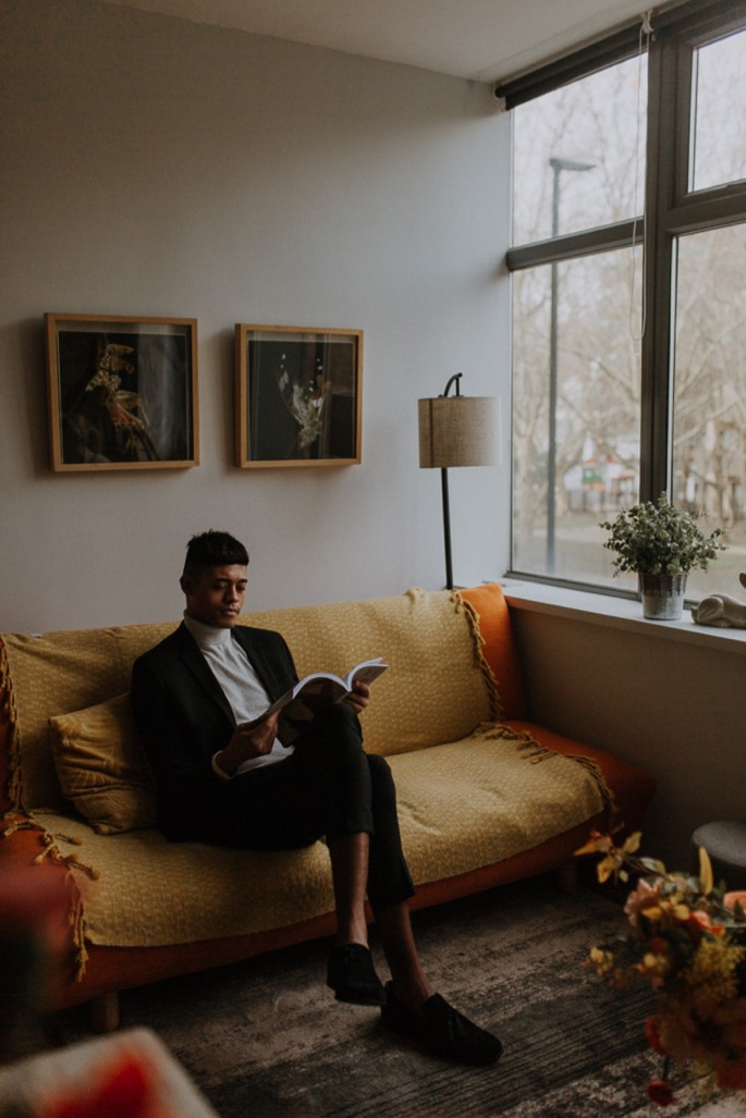 a groom reads in a mustard coloured room