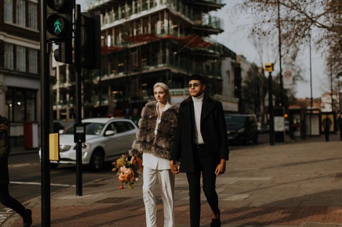 a couple walk through London on their wedding day