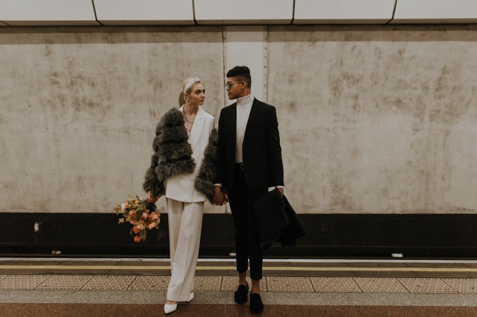 couple look cool stood together on the tube platform