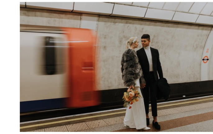 two lovers stood together as a tube arrives