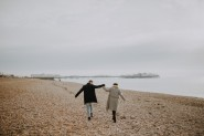 couple hold hands on Brighton beach