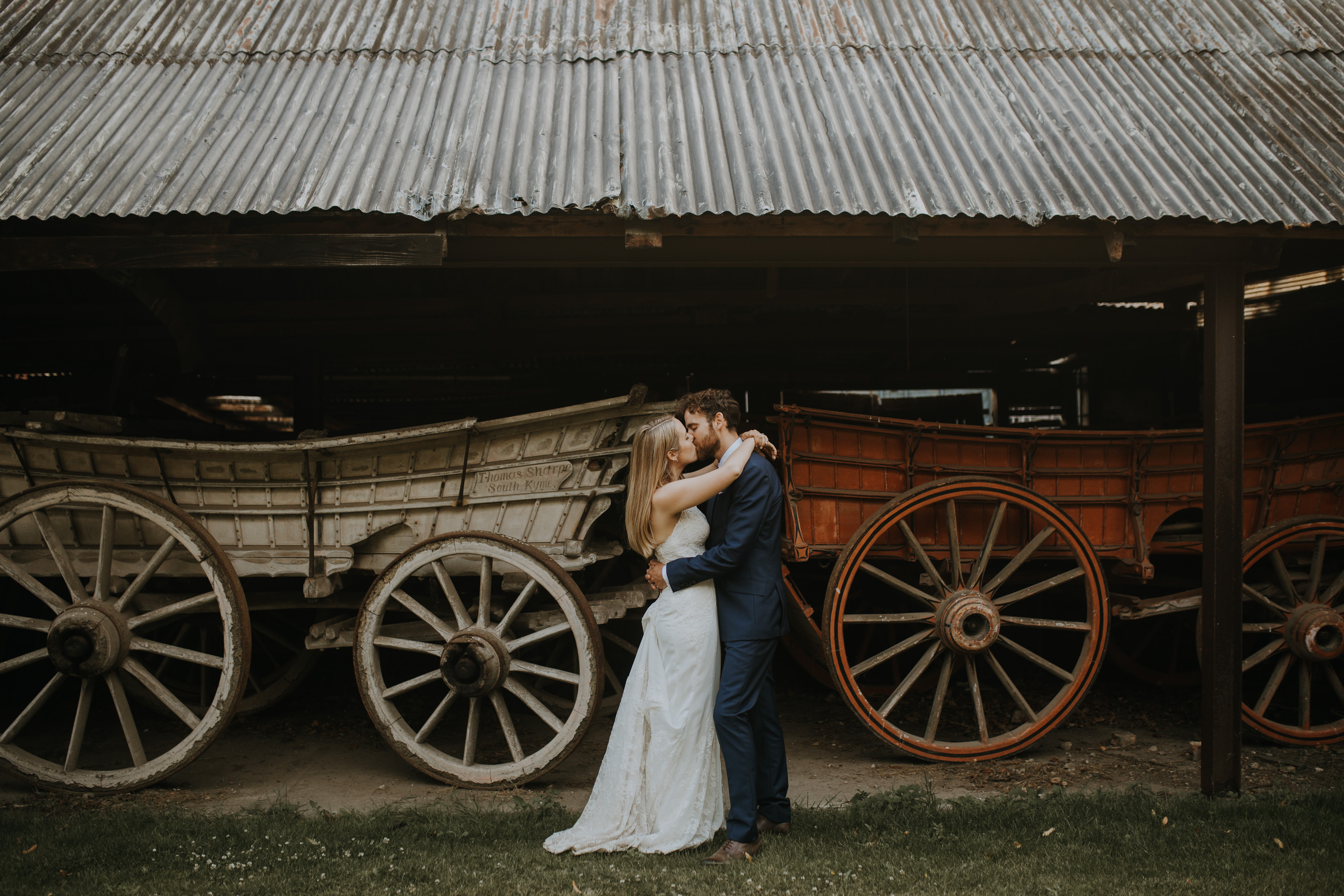 a couple kiss in front of vintage wagons