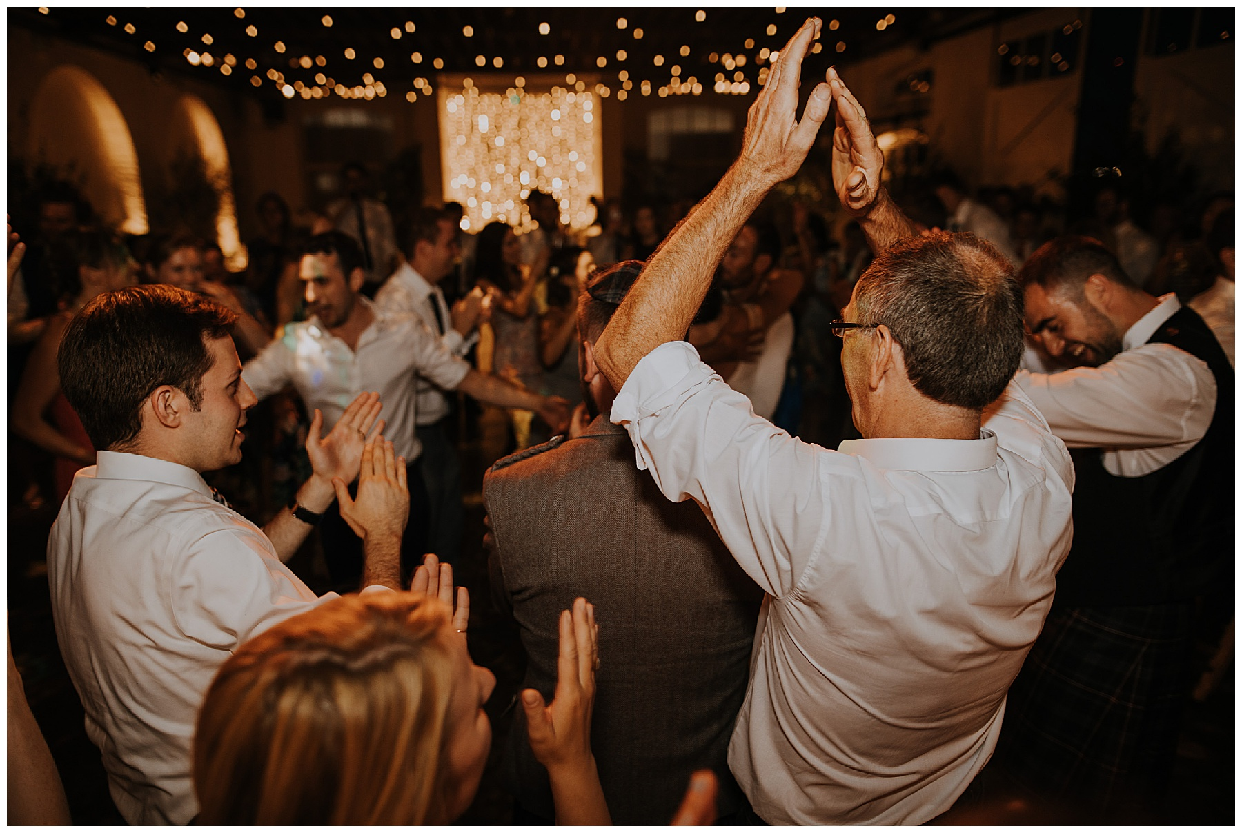 the father of the bride has his hands in the air