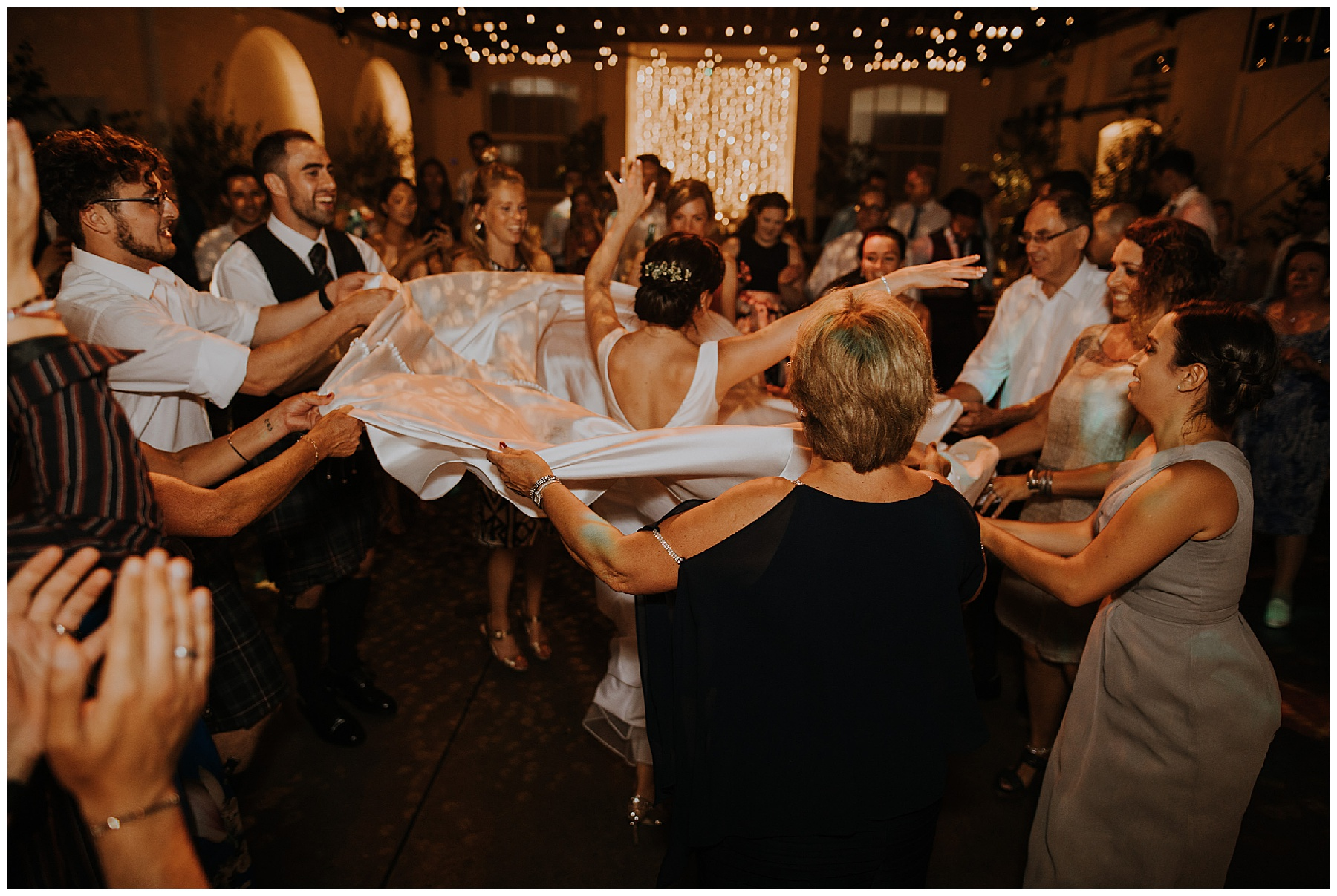 a bride's dress is spun as everyone dances