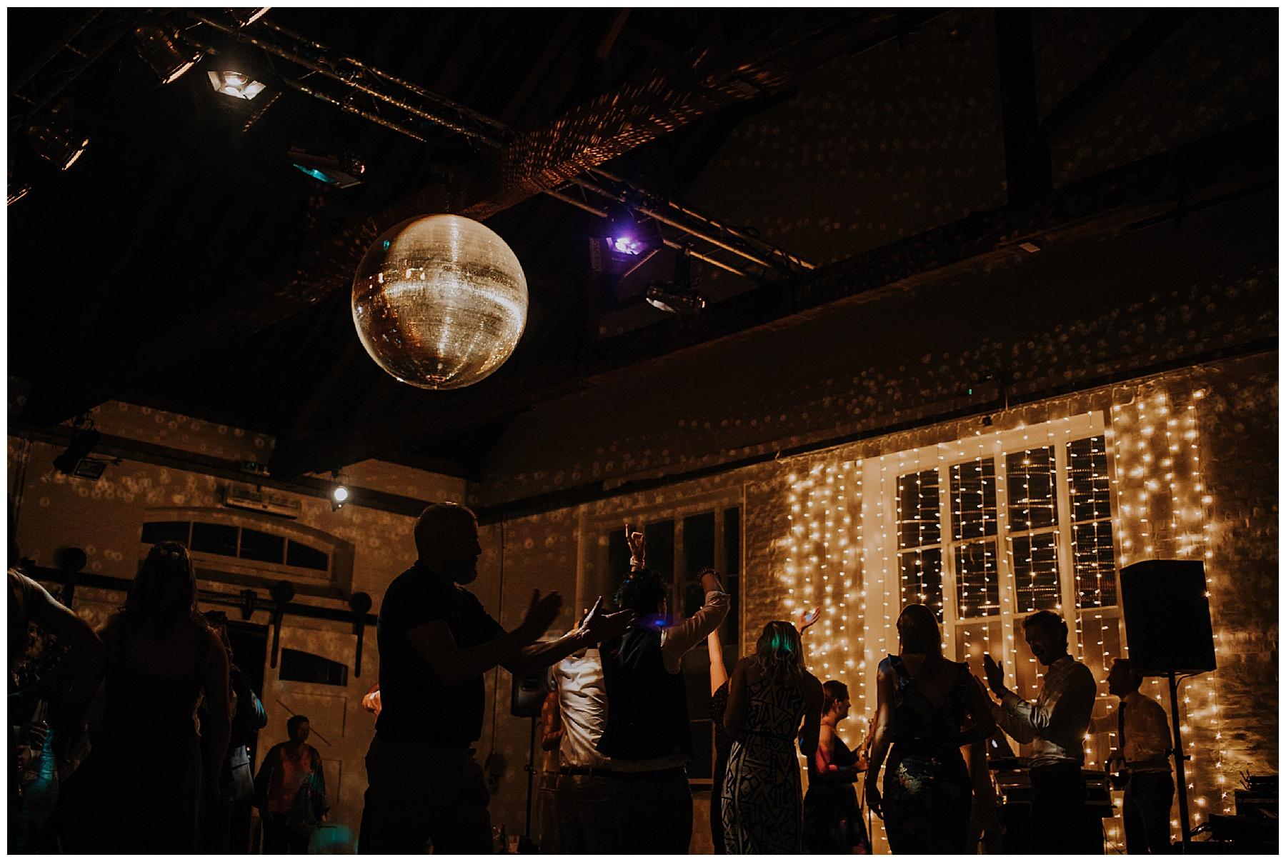 a large disco ball spins above partygoers