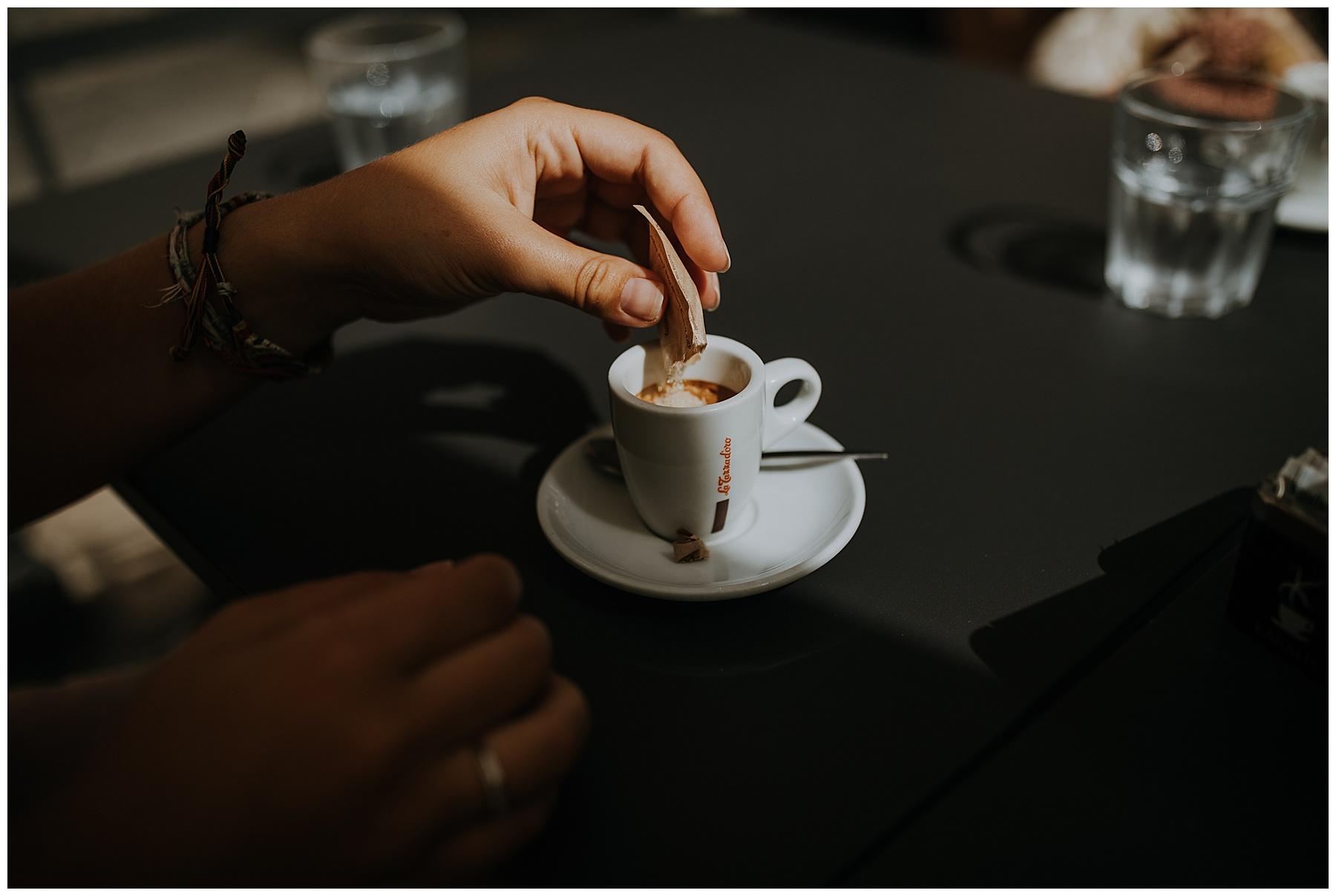 sugar is tipped into espresso