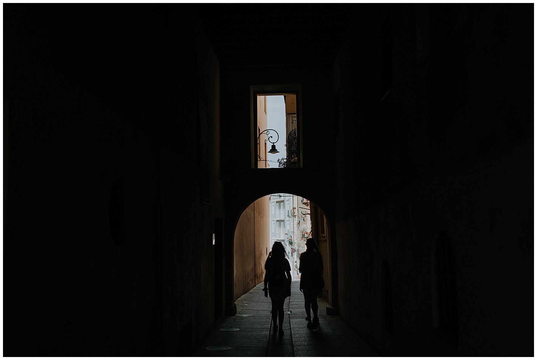 girls walk beneath a cobbled archway
