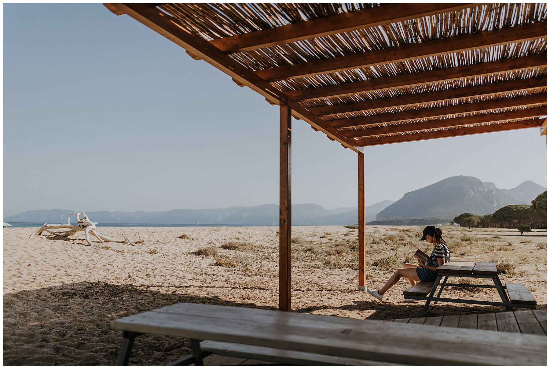 a girl reads at a beach bar with mountains behind