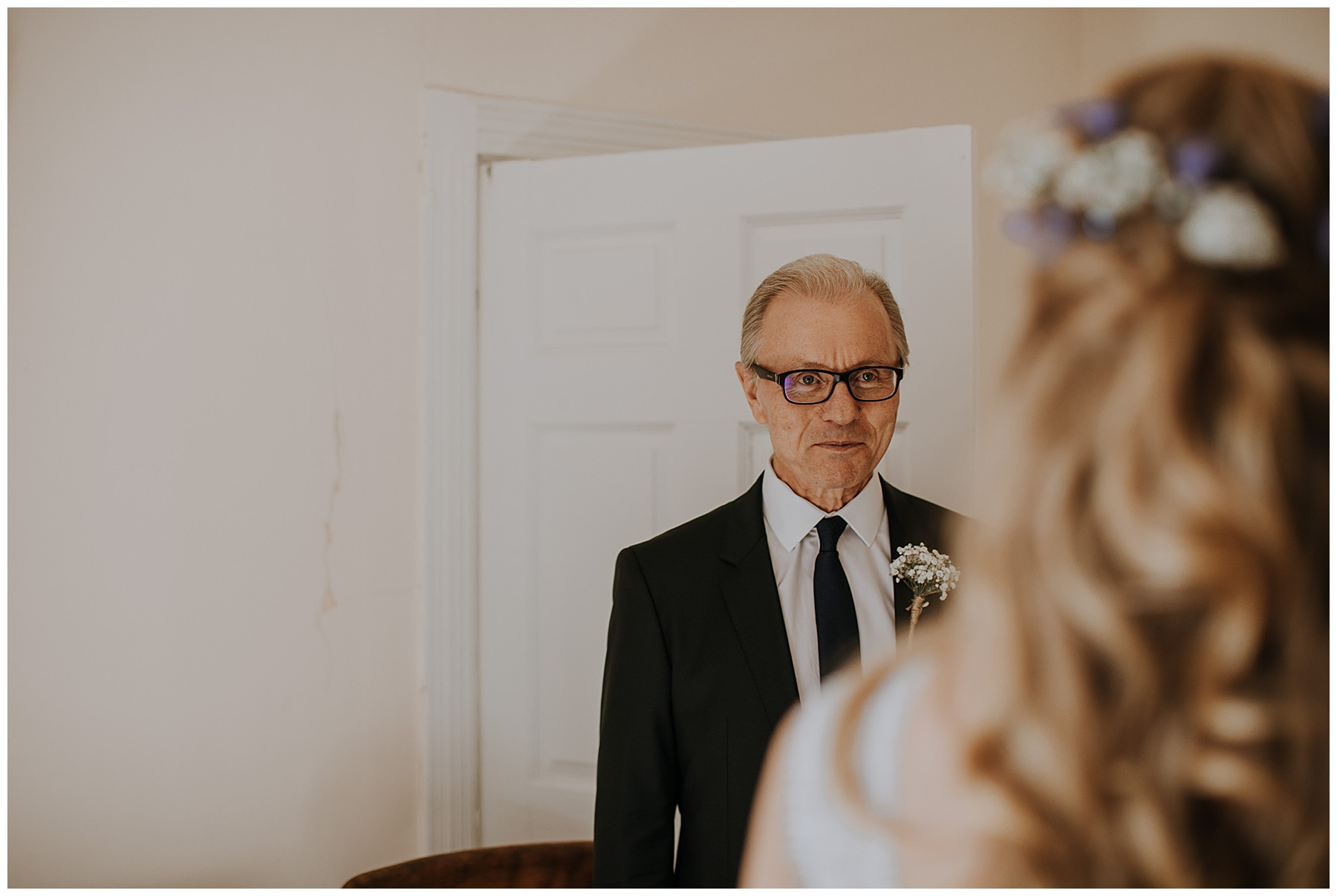 a father sees his daughter in her wedding dress for the first time.